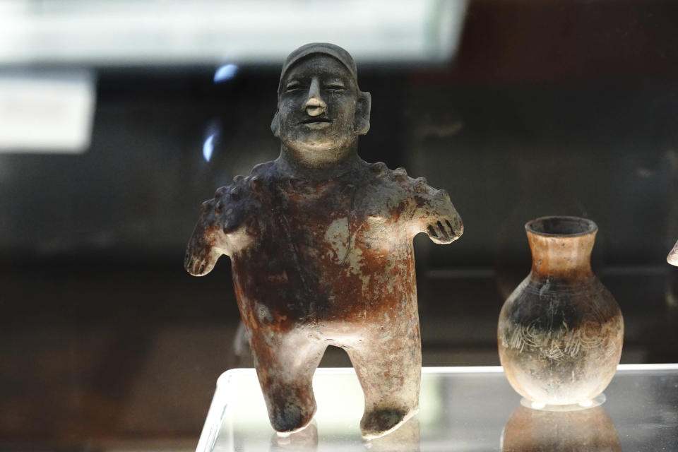"""A Nayarit male figurine and a pot are shown as part of the exhibition """"The Greatness of Mexico"""" displaying for the first time in the country more than 800 pieces repatriated from abroad in the last three years and others that were in safekeeping and confiscation warehouses, at the Anthropology Museum in Mexico City, Friday, Oct. 1, 2021. (AP Photo/Marco Ugarte)"""