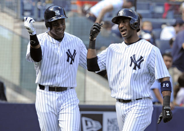 New York Yankees' Eduardo Nunez, right celebrates with Curtis Granderson after Nunez hit a two-run home run during the fourth inning of an inter-league baseball game against the San Francisco Giants Saturday, Sept. 21, 2013, at Yankee Stadium in New York. (AP Photo/Bill Kostroun)