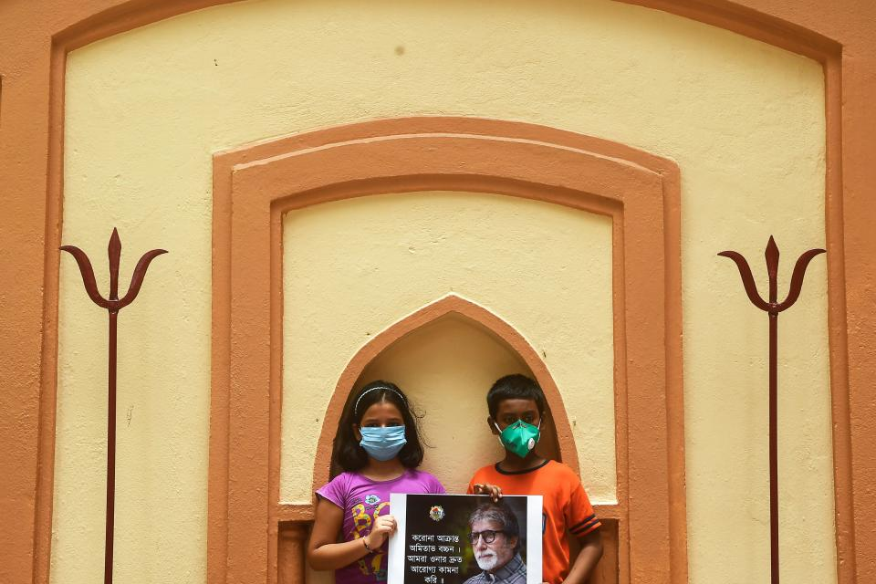 Young fans hold a poster of Bollywood actor Amitabh Bachchan while a priest (unseen) performs special rituals and prayers for his recovery as he tested positive for COVID-19, at a temple in Kolkata on July 12, 2020. - Bollywood megastar Amitabh Bachchan, 77, tested positive for COVID-19 on July 11 and was admitted to hospital in Mumbai, with his actor son Abhishek -- who also announced he had the virus -- saying both cases were mild. (Photo by Dibyangshu SARKAR / AFP)