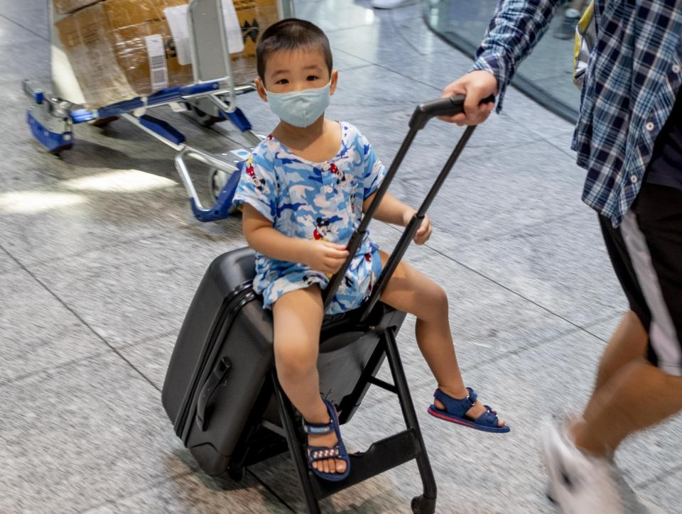A small Asian boy is carried on a trolley at the airportin Frankfurt, Germany, Friday, July 24, 2020. (AP Photo/Michael Probst)