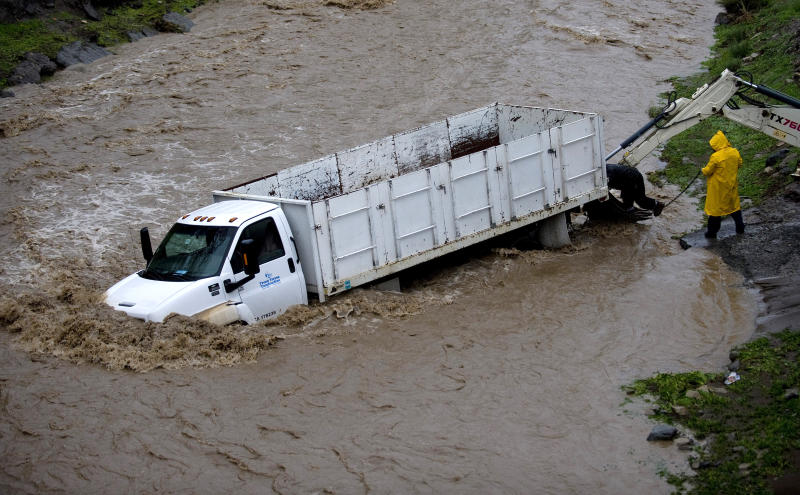 People attempt to pull a truck out of  the rain-swollen Santiago Creek near Modjeska Canyon, Calif. on Tuesday, Dec. 21, 2010. (AP Photo/Orange County Register, Mark Rightmire)  NO SALES; MAGS OUT; LOS ANGELES TIMES OUT