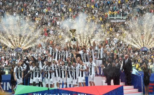 Juventus goalie Gianluigi Buffon holds up the Serie A soccer title trophy, at the Allianz Stadium in Turin, Italy, Saturday, May 19, 2018. Juventus beat already relegated Hellas Verona 2-1 in the final round of the season on Saturday but the result mattered little as the club bid an emotional farewell to Buffon, while it also received a record-extending seventh successive Serie A trophy. (Andrea Di Marco/ANSA via AP)