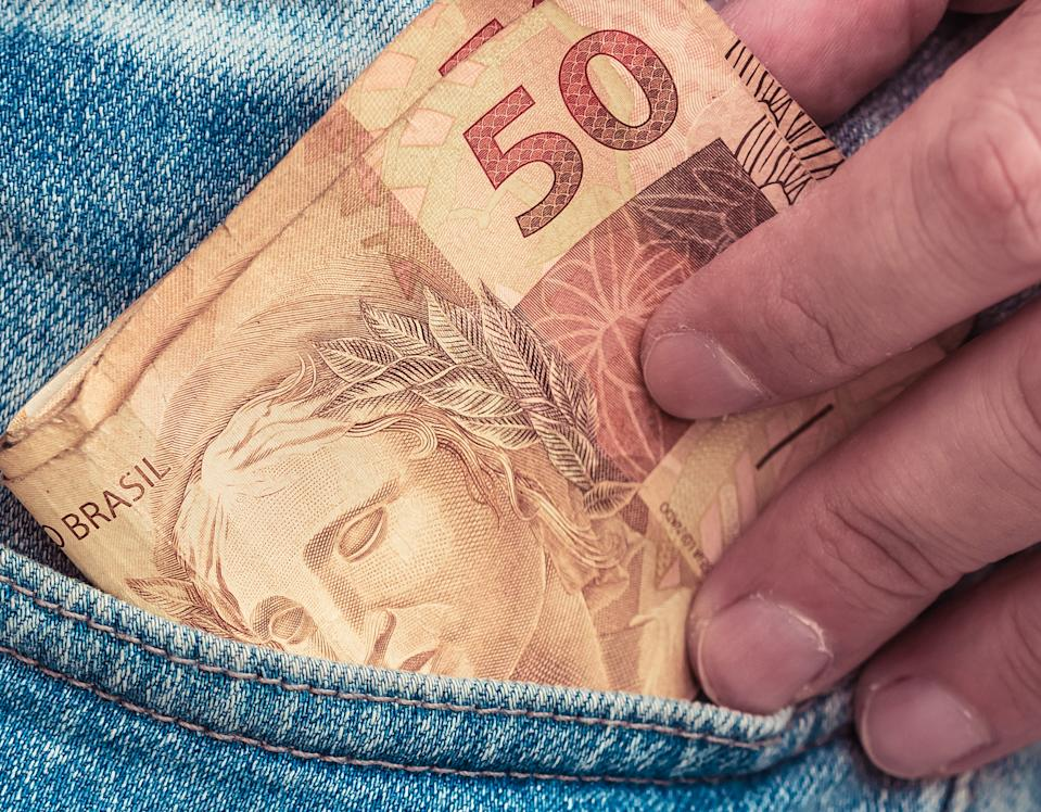 Real - Money from Brazil. Currency, Dinheiro, Brasil, Emprego. Man holding a fifty reais banknotes.