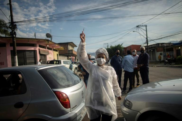 A health worker holds up a syringe with a dose of the Covid-19 vaccine at a vaccination center in Duque de Caxias, Rio de Janeiro state, on March 30, 2021