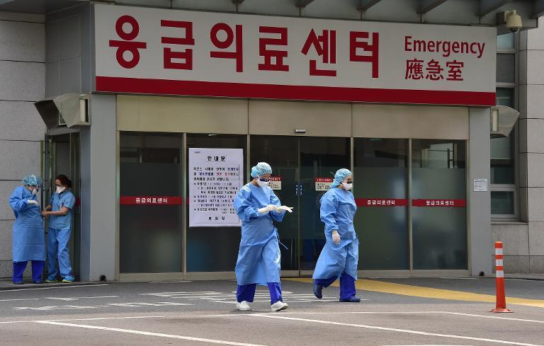 South Korean medical workers wearing protective gear walk to a separated clinic center for MERS at Konkuk University Hospital in Seoul on June 24, 2015