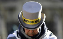 FILE - In this Wednesday, Jan. 29, 2020 file photo, Why Brexit? is written on the hat of Anti-Brexit campaigner Steve Bray as he stands outside Parliament in London. Britain and the European Union have struck a provisional free-trade agreement that should avert New Year's chaos for cross-border commerce and bring a measure of certainty to businesses after years of Brexit turmoil. The breakthrough on Thursday, Dec. 24, 2020 came after months of tense and often testy negotiations that whittled differences down to three key issues: fair-competition rules, mechanisms for resolving future disputes and fishing rights. (AP Photo/Kirsty Wigglesworth, File)
