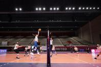 Right side hitter Karsta Lowe, left, watches as middle blocker Lauren Gibbemeyer, top left, makes a hit during volleyball practice in Dallas, Wednesday, Feb. 24, 2021. U.S. (AP Photo/Tony Gutierrez)