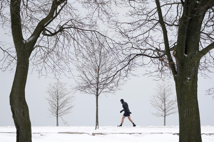 A lone runner leans into a stiff wind near Lake Michigan on the Northside of Chicago Tuesday, Jan. 26, 2021. A major winter storm dumped more than a foot of snow on parts of the middle of the country stretching from central Kansas northeast to Chicago and southern Michigan.(AP Photo/Charles Rex Arbogast)