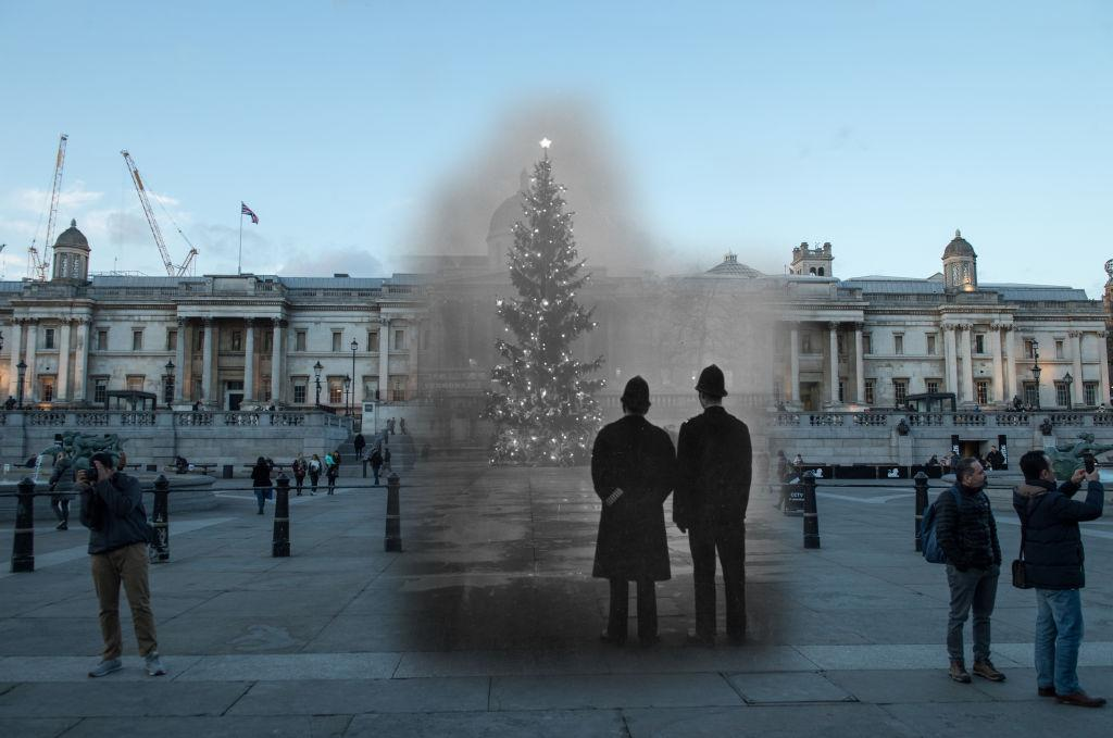<p>Two policemen regard London's 64ft Christmas tree, a gift from Norway, illuminated in Trafalgar Square, in front of the National Gallery on 1 December, 1948. (Getty) </p>