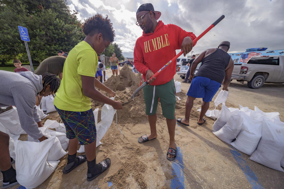Jawan Williams shovels sand for a sandbag held by his son Jayden Williams, before landfall of Hurricane Ida at the Frederick Sigur Civic Center in Chalmette, La., which is part of the Greater New Orleans metropolitan area, Saturday, Aug. 28, 2021. The storm is expected to bring winds as high as 140 mph when it slams ashore late Sunday. (AP Photo/Matthew Hinton)