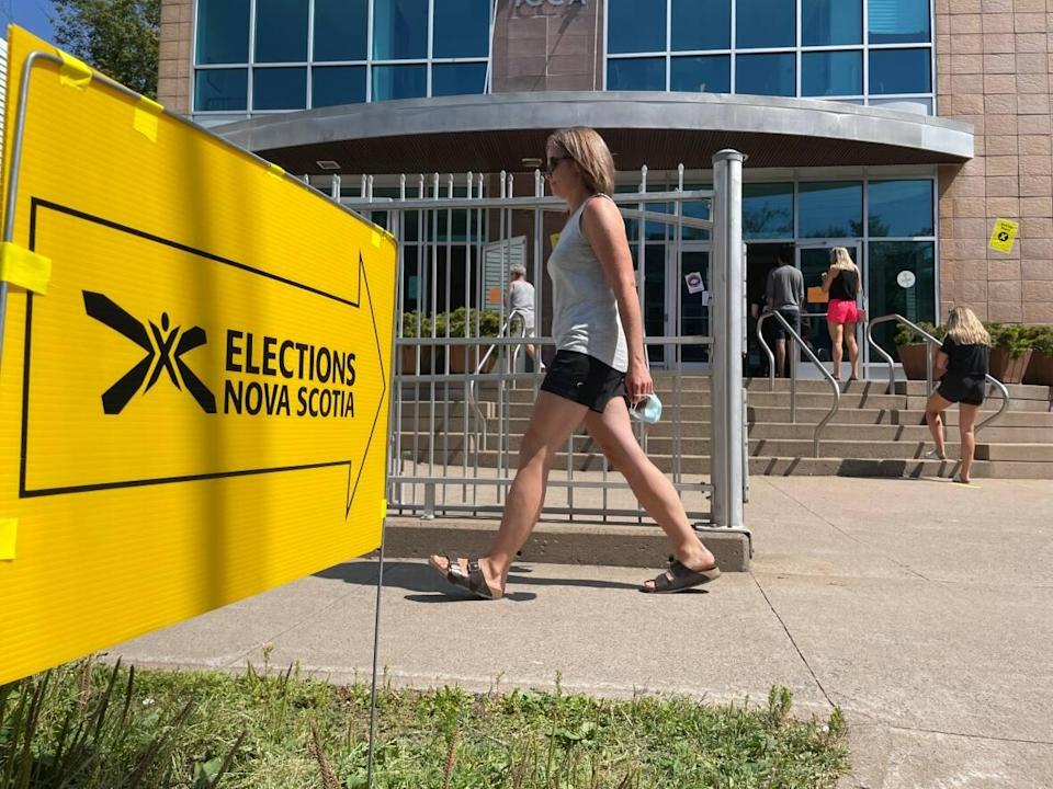 A woman walks by a voting station where people are lined up to vote on Aug. 17 in Halifax.  (Rose Murphy/CBC - image credit)