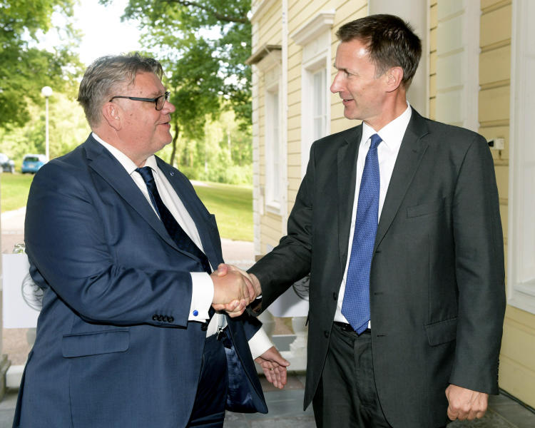 Finland's Minister for Foreign Affairs Timo Soini, left, shakes hands with British Foreign Secretary Jeremy Hunt, during their press conference, in Vantaa, Finland, Tuesday, Aug. 14, 2018. (Vesa Moilanen/Lehtikuva via AP)