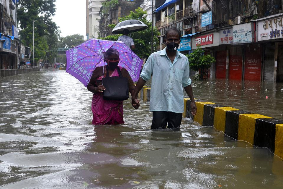 Senior citizens wade in knee deep water along a flooded road during a heavy monsoon rainfall in Mumbai on August 4, 2020. (Photo by SUJIT JAISWAL/AFP via Getty Images)
