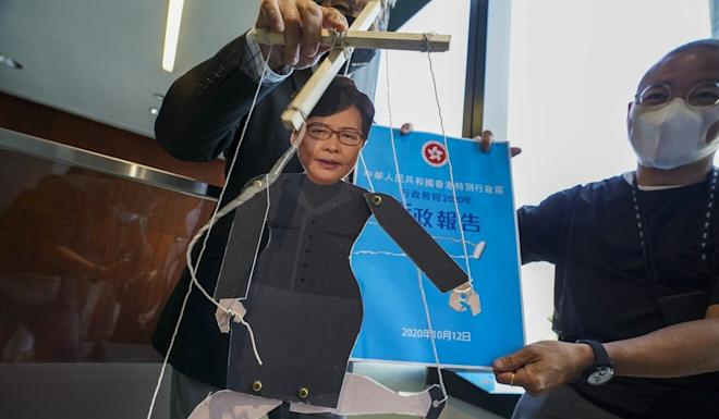 Pan-democratic lawmakers hold up a puppet mocking Chief Executive Carrie Lam after she announced the postponement of her policy address. Photo: Felix Wong
