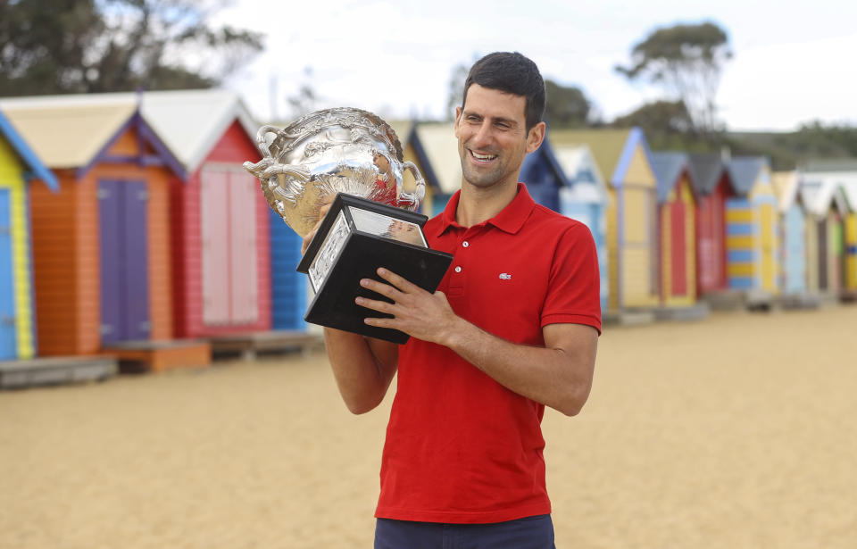 Serbia's Novak Djokovic poses for photos with the Norman Brookes Challenge Cup at Brighton Beach after defeating Russia's Daniil Medvedev on Sunday Feb. 21, 2021 in the men's singles final at the Australian Open tennis championship in Melbourne, Australia, Monday, Feb. 22, 2021.(AP Photo/Hamish Blair)
