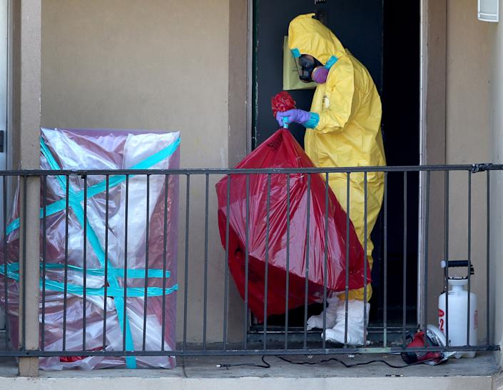 A cleaning crew removes items from the apartment where Ebola patient Thomas Eric Duncan was staying before being admitted to a hospital on October 6, 2014 in Dallas, Texas.