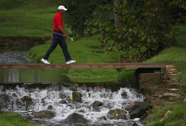 Tiger Woods of the U.S. crosses over a creek as he and teammate Matt Kuchar play against International team members Adam Scott of Australia and Hideki Matsuyama of Japan in their four ball match at the 2013 Presidents Cup golf tournament at Muirfield Village Golf Club in Dublin, Ohio October 5, 2013. REUTERS/Jeff Haynes (UNITED STATES - Tags: SPORT GOLF)