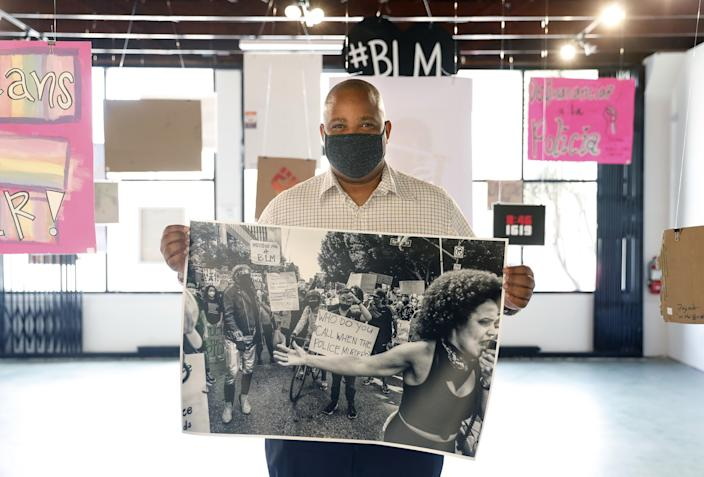 """Adrian White displays one of his protest images at SoLA Contemporary. The photographer has been documenting Black Lives Matter protests around the city. <span class=""""copyright"""">(Christina House / Los Angeles Times)</span>"""