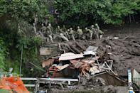 Japanese rescuers sift through mud and debris as they search for missing people at the scene of a landslide in Atami, Shizuoka Prefecture, on July 5, 2021