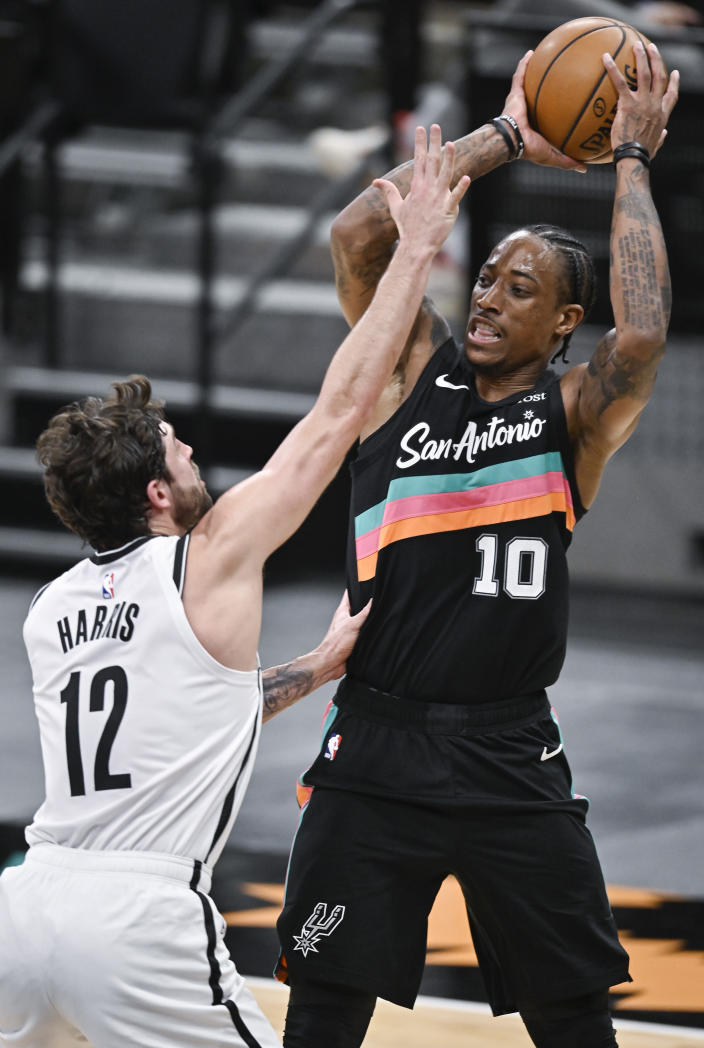 San Antonio Spurs' DeMar DeRozan (10) looks to pass as he is defended by Brooklyn Nets' Joe Harris during the first half of an NBA basketball game, Monday, March 1, 2021, in San Antonio. (AP Photo/Darren Abate)