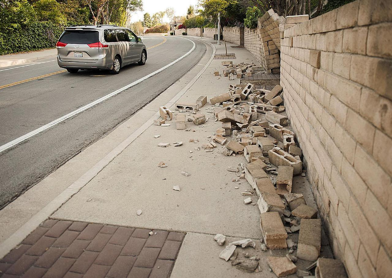 A broken block wall blocks the sidewalk Saturday, March 29, 2014, after an earthquake hit Orange County Friday night in Fullerton, Calif. More than 100 aftershocks have rattled Orange County south of Los Angeles where a magnitude-5.1 earthquake struck Friday. Despite the relatively minor damage, no injuries have been reported. (AP Photo/The Orange County Register, Ken Steinhardt) MAGS OUT; LOS ANGELES TIMES OUT