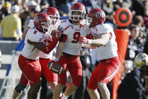 Utah linebacker Trevor Reilly, center, is congratulated after his interception against Colorado by teammates Nate Fakahafua, left, and Viliseni Fauonuka during the first quarter of an NCAA college football game, Friday, Nov. 23, 2012, in Boulder, Colo. The interception set up Utah's first touchdown. (AP Photo/David Zalubowski)