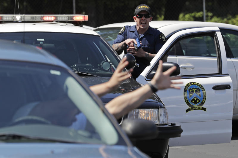 In this July 16, 2019, photo, a King County Sheriff's deputy holds a training weapon as he practices a traffic stop during a class at Washington state's Basic Law Enforcement Academy in Burien, Wash. Accidental shootings by police happen across the United States every year, an Associated Press investigation has found, and cadets at Washington's academy, which is required for all entry-level Washington state law enforcement officers, must have 90 hours of firearms training, but requirements in other states vary widely. (AP Photo/Ted S. Warren)