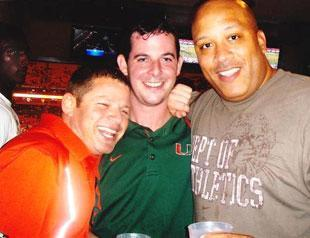 Nevin Shapiro (left) poses with Miami Hurricanes staffer Sean Allen (middle) and Hurricanes assistant basketball coach Jake Morton (right) in his luxury suite during the 2009 season. Along the left margin of the photo (in white shirt) is then-Hurricanes football recruiting target Jeffrey Godfrey, who was a senior in high school at the time of this picture. Shapiro said he knew NCAA rules prohibited Godfrey from being in his suite at the time this photo was taken.