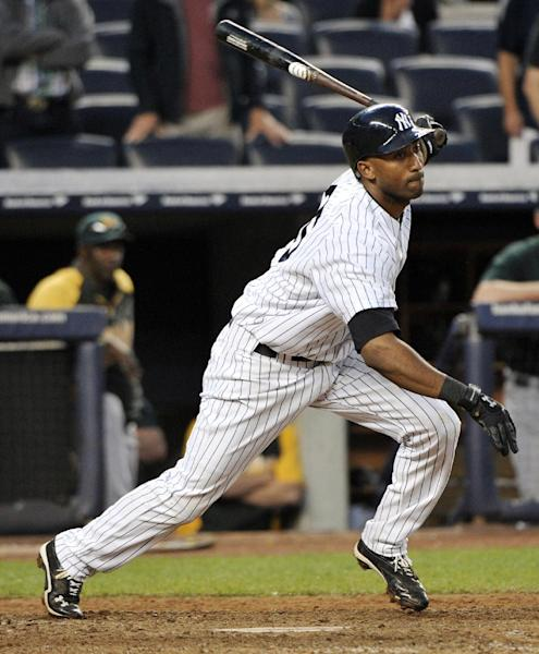 New York Yankees' Eduardo Nunez hits a ground ball that was booted for an error by Oakland Athletics first baseman Brandon Moss, allowing Ichiro Suzuki to score the winning run, during the 14th inning of a baseball game on Saturday, Sept. 22, 2012, at Yankee Stadium in New York. The Yankees won 10-9. (AP Photo/Bill Kostroun)