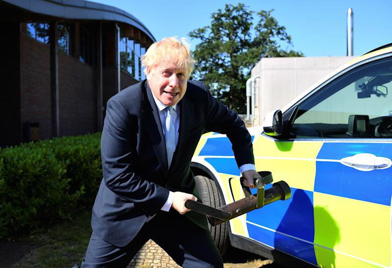 Boris Johnson holds a battering ram during a visit to the Thames Valley Police Training Centre in Reading, Berkshire (Picture: PA)