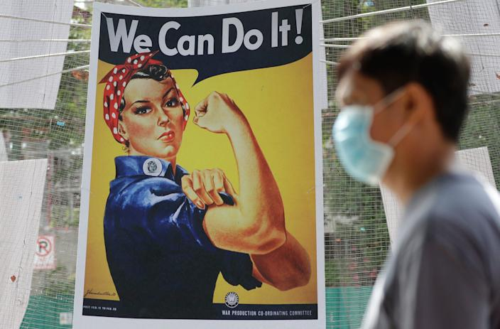 A mask-wearing man in the Philippines walks by an iconic poster from WWII America that depicts Rosie the Riveter, a fictional factory worker meant to inspired Americans of both sexes to pitch in to the war effort during the 1940s. Our coronavirus crisis could inspire the same kind of unified national effort at recovering from the epidemic, historians say.