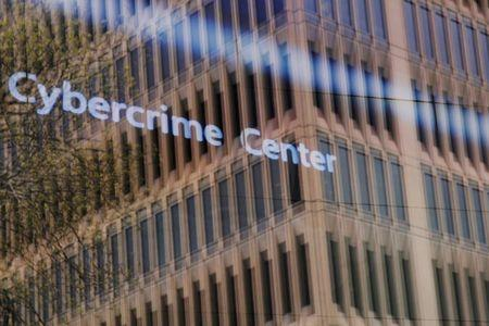 FILE PHOTO: An advertisement about the Microsoft Cybercrime Center plays behind a window reflecting a nearby building at the Microsoft office in Cambridge, Massachusetts, U.S. on May 15, 2017. REUTERS/Brian Snyder/File Photo