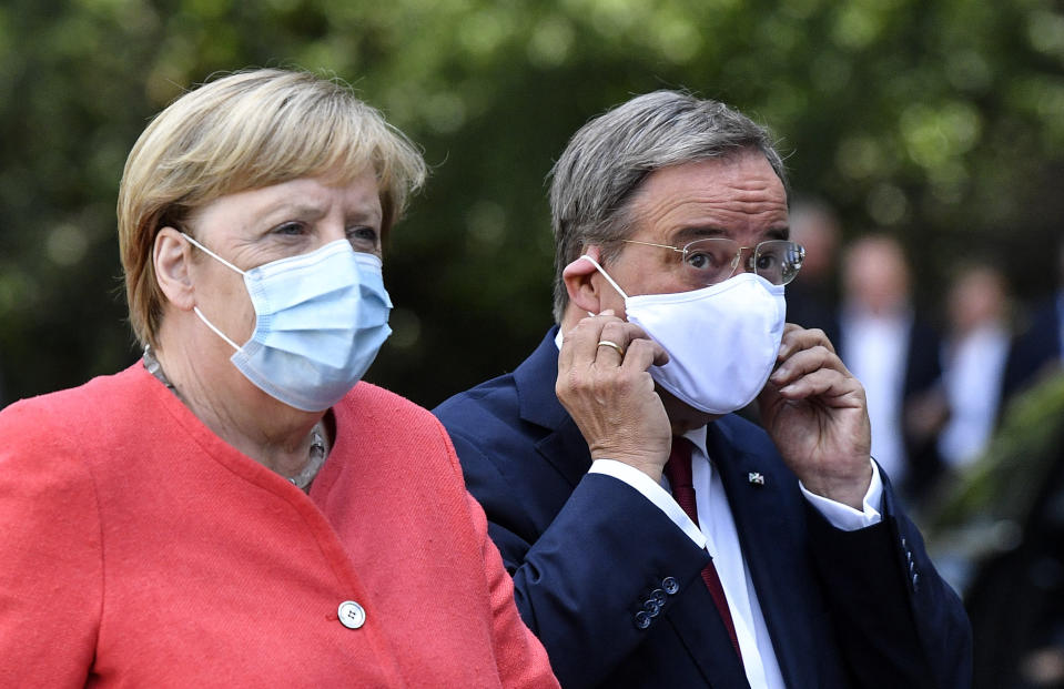 German chancellor Angela Merkel, left, wears a face mask due to the coronavirus pandemic as she meets Governor Armin Laschet, right, during her visit at Germany's most populated province North Rhine-Westphalia in Duesseldorf, Germany, Tuesday, Aug. 18, 2020. (AP Photo/Martin Meissner)