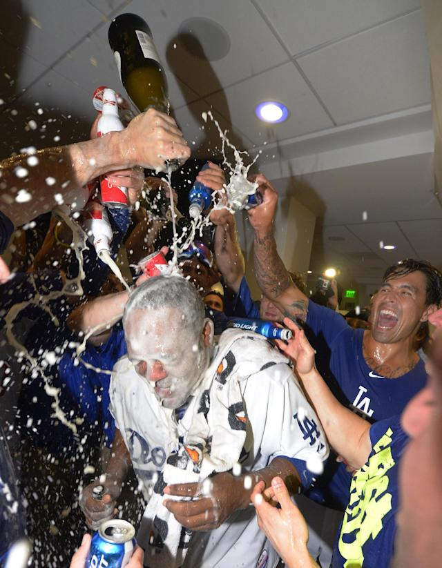 Los Angeles Dodgers' Juan Uribe, center, is doused by his teammates as they celebrate in the clubhouse after the Dodgers defeated the Atlanta Braves 4-3 in Game 4 of the National League baseball division series and advanced to the NL championship series, Monday, Oct. 7, 2013, in Los Angeles. Uribe hit a two-run home run in the eighth inning to put the Dodgers ahead. (AP Photo/Mark J. Terrill)