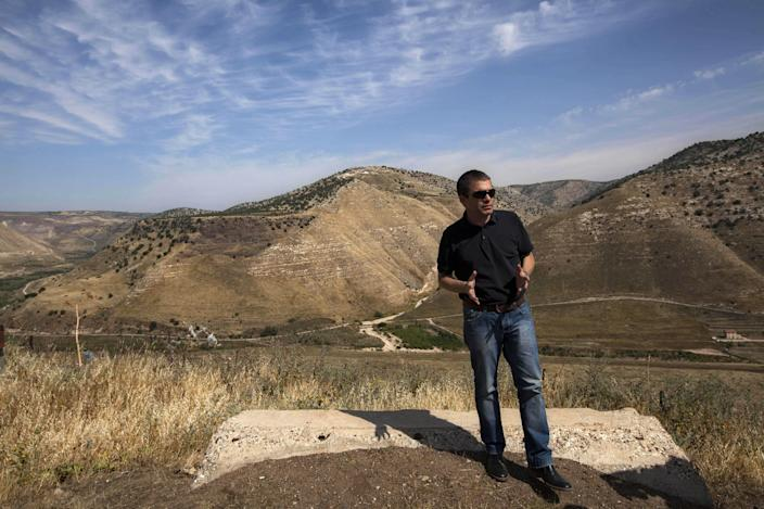 In this photo taken Wednesday, April 24, 2013, Gal Hirsch, a reserve Israeli General, stands at an army outpost overlooking Syria and Jordan in the Golan Heights. Against a breathtaking vista of green fields and a snowcapped mountain range, all is silent but for a strong gust of wind whipping across the landscape. The tranquility is suddenly interrupted by a burst of gunfire from beyond a newly built fortified fence: Jihadi rebels are battling with Bashar Assad's battered troops in a nearby Syrian village. Watching it all unfold are Israeli soldiers atop tanks - a sight unseen here in a generation - and the sounds of explosions from a large-scale Israeli drill are distinctly heard in the background. (AP Photo/Sebastian Scheiner)