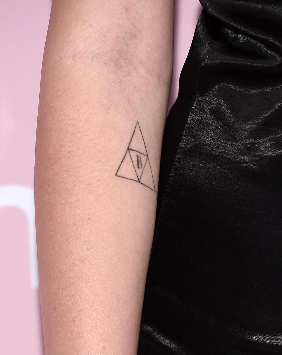 <p>On her right arm, Cyrus has a matching tattoo with older brother Braison. The design is of the triforce symbol, which represents growth and harmony, with the letter B in the middle. She got it in 2017.</p>