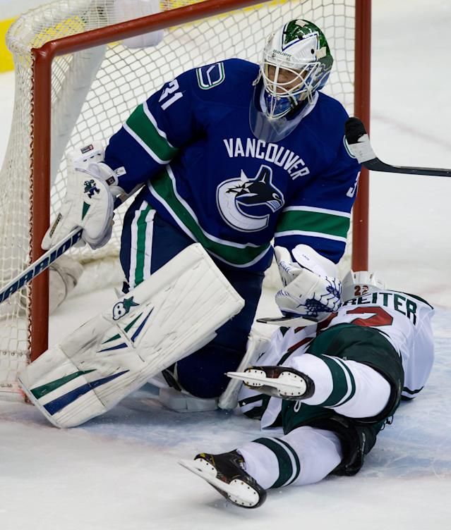 Minnesota Wild's Nino Niederreiter, right, of Switzerland, crashes into Vancouver Canucks goalie Eddie Lack, of Sweden, during the second period of an NHL hockey game Friday, Feb. 28, 2014, in Vancouver, British Columbia. (AP Photo/The Canadian Press, Darryl Dyck)