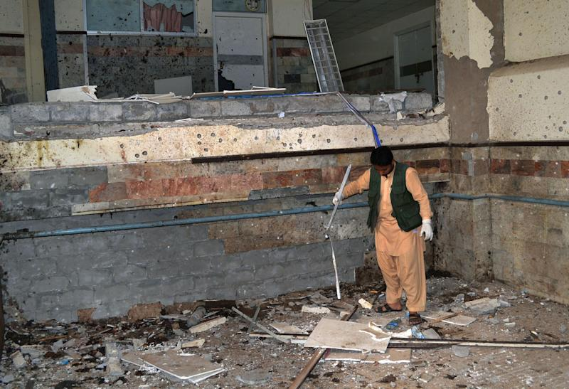 A Pakistani security official examines the site of Saturday's bombing at the Bolan Medical complex in Quetta, Pakistan on Sunday, June 16, 2013. The radical Lashkar-e-Jhangvi group claimed responsibility for the attacks on the hospital and a women's university bus. (AP Photo/Arshad Butt)