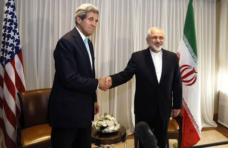 U.S. Secretary of State John Kerry shakes hands with Iranian Foreign Minister Mohammad Javad Zarif before a meeting in Geneva