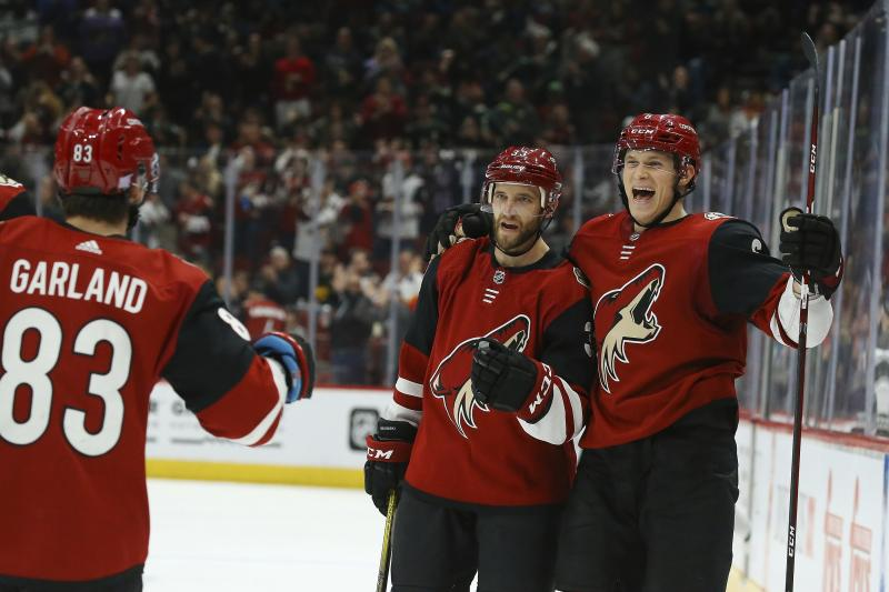 Arizona Coyotes defenseman Jakob Chychrun, right, celebrates his goal against the Los Angeles Kings with defenseman Alex Goligoski, center, and Coyotes right wing Conor Garland (83) during the second period of an NHL hockey game Monday, Nov. 18, 2019, in Glendale, Ariz. (AP Photo/Ross D. Franklin)