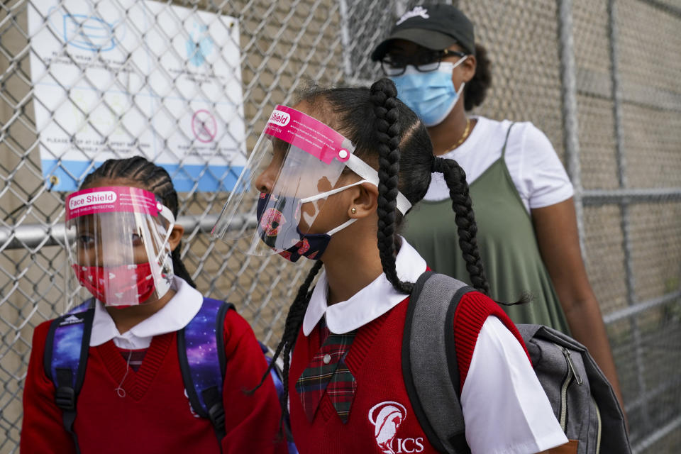 FILE - In this Sept. 9, 2020, file photo, students wear protective masks as they arrive for classes at the Immaculate Conception School while observing COVID-19 prevention protocols in The Bronx borough of New York. The pandemic began with devastation in the New York City area, and was followed by a summertime crisis in the Sun Belt. But it is now striking cities with much smaller populations, often in conservative corners of America where anti-mask sentiment runs high, creating problems at hospitals and schools in the Midwest and West. (AP Photo/John Minchillo, File)