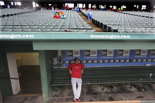 Los Angeles Angels relief pitcher Ernesto Frieri sits in an empty dugout because of a rain delayed start of the baseball game against the Texas Rangers Saturday, Sept. 29, 2012, in Arlington, Texas. (AP Photo/LM Otero)