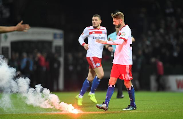 Soccer Football - Bundesliga - Werder Bremen vs Hamburger SV - Weser-Stadion, Bremen, Germany - February 24, 2018 Hamburg's Aaron Hunt next to a flare thrown onto the pitch REUTERS/Fabian Bimmer DFL RULES TO LIMIT THE ONLINE USAGE DURING MATCH TIME TO 15 PICTURES PER GAME. IMAGE SEQUENCES TO SIMULATE VIDEO IS NOT ALLOWED AT ANY TIME. FOR FURTHER QUERIES PLEASE CONTACT DFL DIRECTLY AT + 49 69 650050