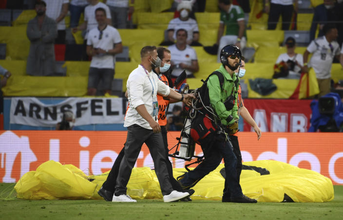 Paraglider walks on the pitch prior the start of the Euro 2020 soccer championship group F match between Germany and France at the Allianz Arena stadium in Munich, Tuesday, June 15, 2021. (Franck Fife/Pool via AP)