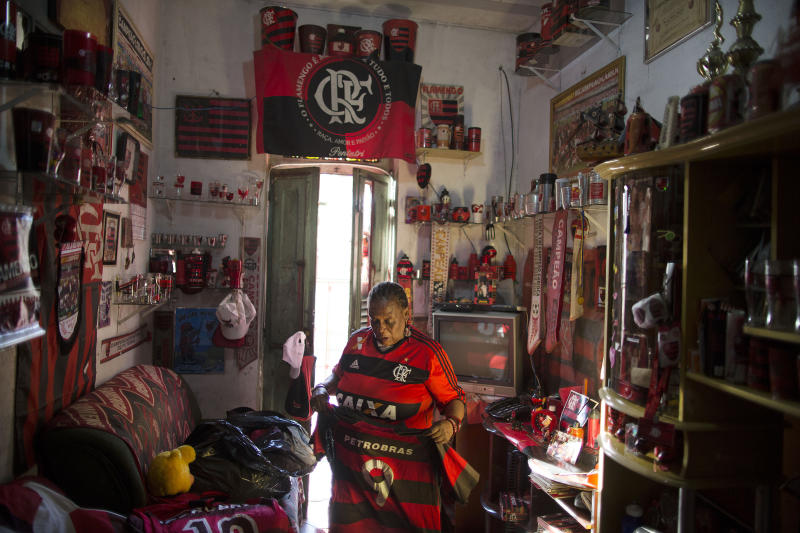 "In this April 28, 2014 photo, Maria Boreth de Souza, alias Zica, organizes her favorite Flamengo jerseys inside her home full of her soccer team's memorabilia in the Olaria neighborhood of Rio de Janeiro, Brazil. Souza is known as ""Zica"" in honor of former Brazilian football great Zico, whose mother persuaded her to leave the streets and return to her home 46 years ago, where she cared for her parents. (AP Photo/Leo Correa)"