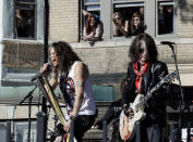 Aerosmith's Steven Tyler, left, and Joe Perry perform a free concert Monday, Nov. 5, 2012 in Boston's Allston neighborhood as fans watch from the apartment building which was their home in the early 1970's. (AP Photo/Elise Amendola)