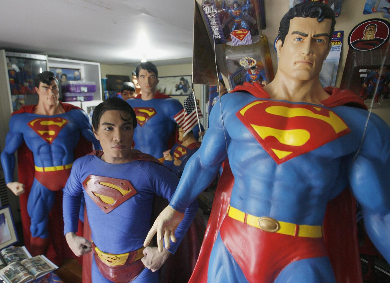 "Herbert Chavez poses with his life-sized Superman statues inside his house in Calamba Laguna, south of Manila October 12, 2011. In his idolization of the superhero, Chavez, a self-professed ""pageant trainer"" who owns two costume stores, has undergone a series of cosmetic surgeries for his nose, cheeks, lips and chin down to his thighs and even his skin color to look more like the ""Man of Steel"". The final result bears little resemblance to his old self. REUTERS/Cheryl Ravelo (PHILIPPINES - Tags: SOCIETY)"