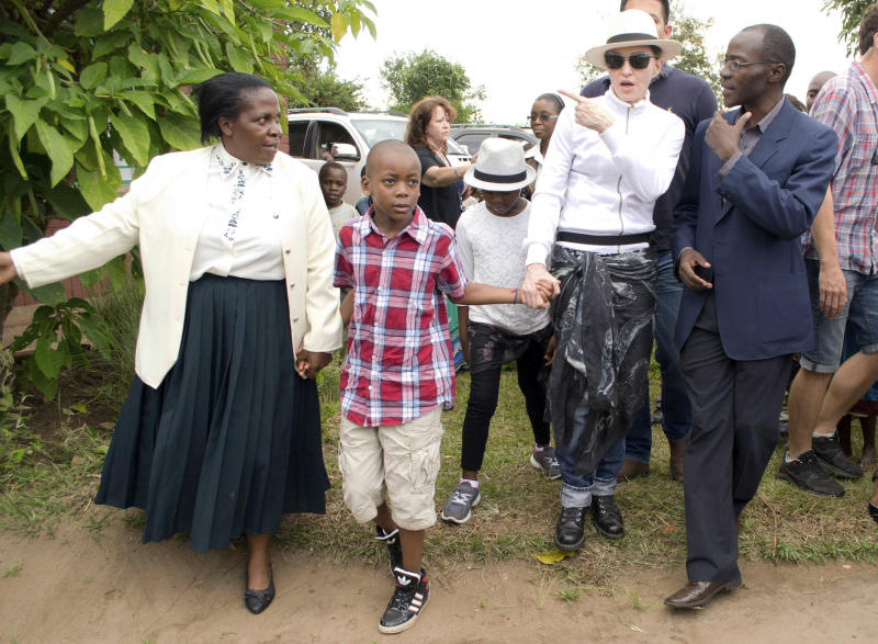 US performer Madonna tours the Mphandura orpahange near Lilongwe, Malawi Friday April 5, 2013. Madonna, is spending her fourth day in the southern African country from where she adopted two children David Banda, second from left and Mercy James, third from left. (AP Photo/Thoko Chikondi)