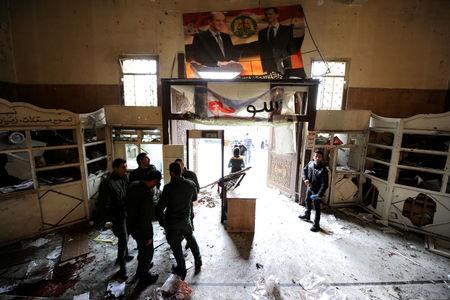 Security personnel stand near a damaged entrance after a suicide blast at the Palace of Justice in Damascus, Syria March 15, 2017. REUTERS/Omar Sanadiki