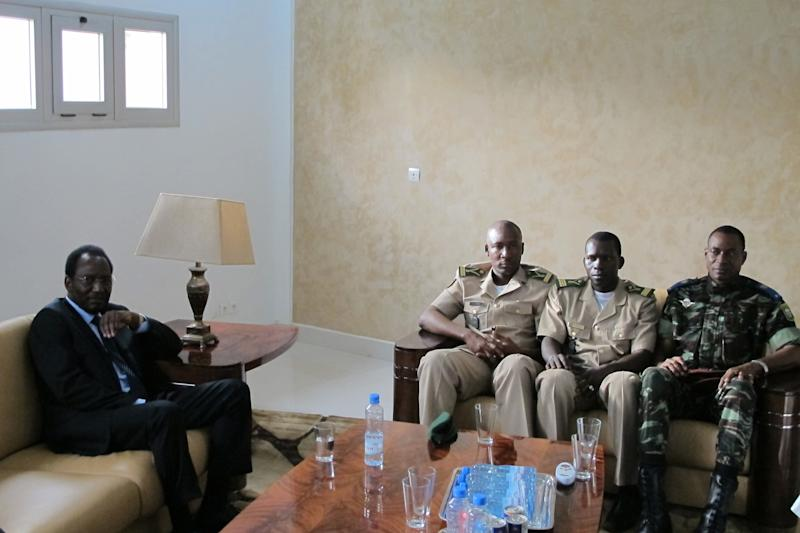 Dioncounda Traore, left, Mali's parliamentary head who was forced into exile after last month's coup, sits with junta representatives including spokesman Lt. Amadou Konare, third right, in Bamako, Mali Saturday, April 7, 2012. Traore's return comes after coup leader Capt. Amadou Haya Sanogo signed an accord late Friday, agreeing to return the nation to constitutional rule. Mali's constitution says that in the event that the president of the republic is unable to carry out his functions, the head of the assembly becomes interim president for a transitional period until new elections are held.(AP Photo/Rukmini Callimachi)